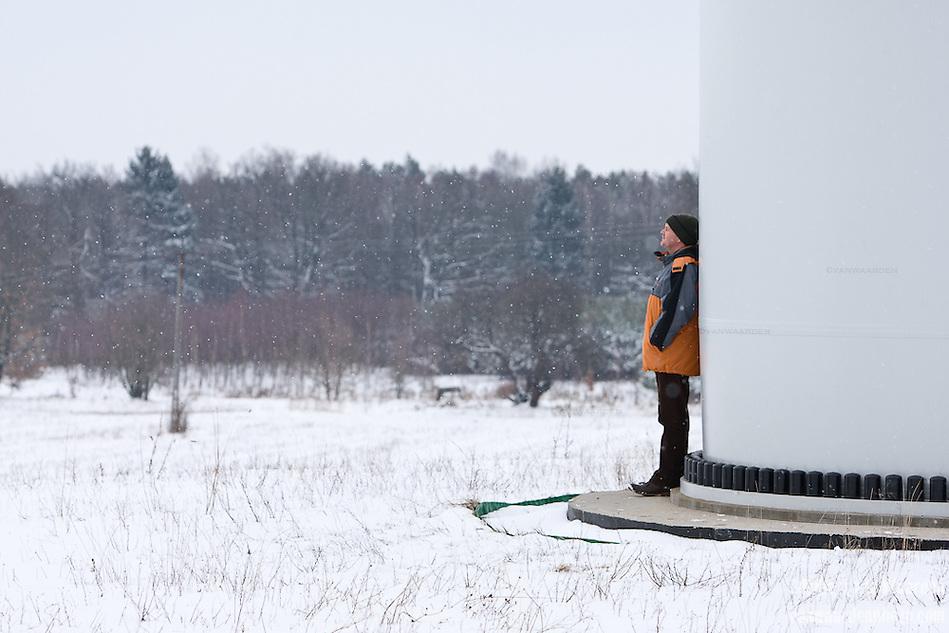 Miros?awa Horodiuk rests against a wind turbine on his farm. (Robert van Waarden)