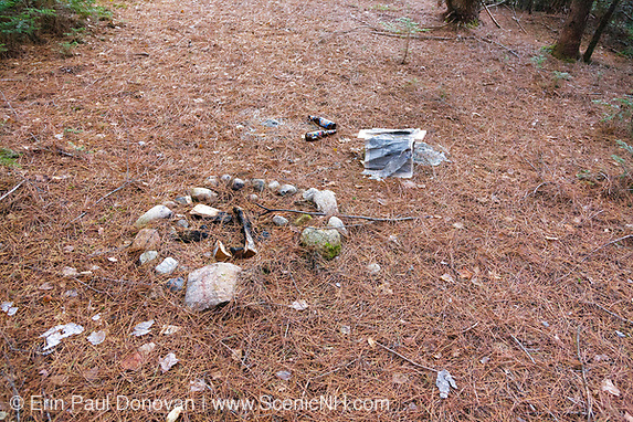 Poor Leave No Trace Ethics - Fresh firepit and campsite trash at Oliverian Brook Trailhead in the White Mountains, New Hampshire.