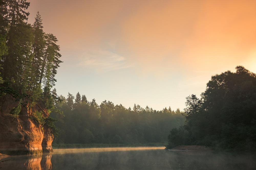 Warm light from rising sun exposes the colorful sandstone cliffs and fog covered River Gauja, near Līgatne, Latvia Ⓒ Davis Ulands | davisulands.com (Davis Ulands/Ⓒ Davis Ulands | davisulands.com)