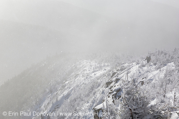 Strong winds blow snow across the valley along the Old Bridle Path during the winter months in the White Mountains, New Hampshire USA. Hikers can be seen ascending the trail.