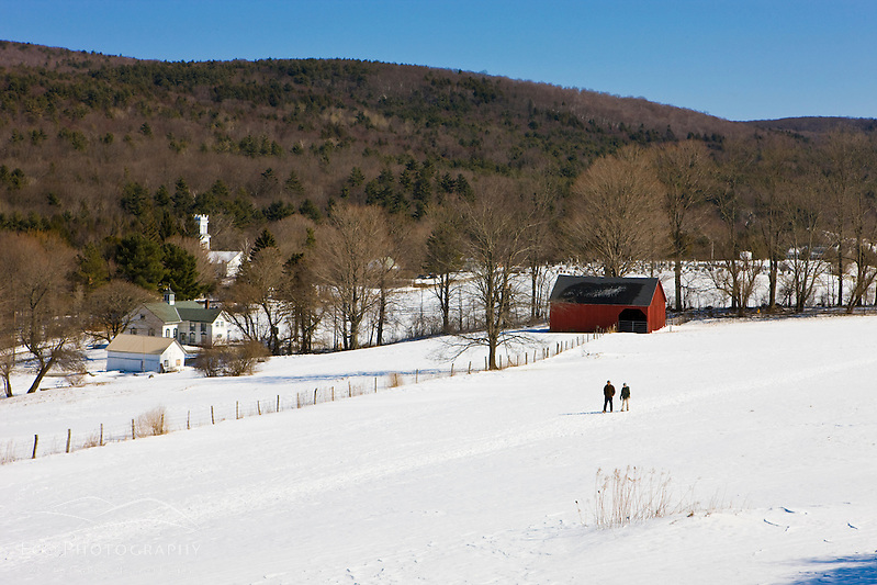 A couple walks through a snowy field at the Tyringham Cobble Reservation in Tyringham, Massachusetts. Berkshire Mountains. The Trustees of Reservations. (Jerry and Marcy Monkman)