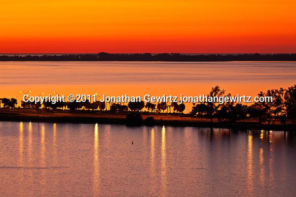 Red twilight immediately before sunrise, looking over Miami's Rickenbacker Causeway and Key Biscayne toward the Atlantic Ocean on New Year's Eve 2011. (© Jonathan Gewirtz)