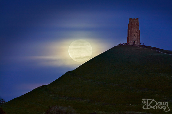 The full moon rises on Halloween 2020 veiled by thin clouds. A group of people watch it rise from beside the tower of St Michaels Church on Glastonbury Tor. (Doug King)