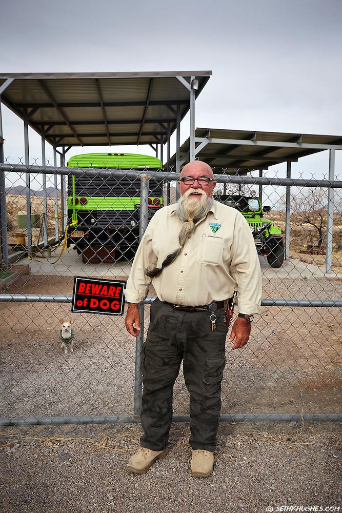 A friendly, large, bearded man stands smiling outside of his desert compound in New Mexico with a guard dog keeping a watchful eye. (Seth K Hughes)