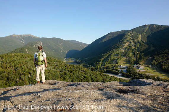A hiker enjoys the view of Franconia Notch from Bald Mountain in the New Hampshire White Mountains.