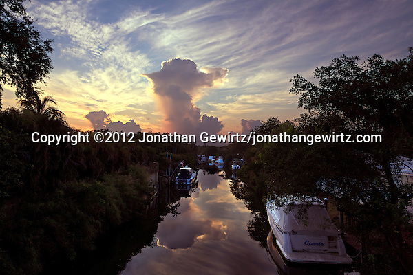 The image of a dissipating storm reflects from the tranquil surface of a canal shortly after sunrise in Coral Gables, Florida. (© 2012 Jonathan Gewirtz / jonathan@gewirtz.net)