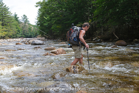 Hiker crossing the East Branch of the Pemigewasset River in the Pemigewasset Wilderness of Lincoln, New Hampshire.