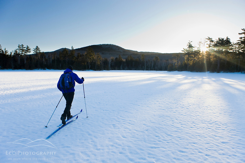 A man cross-country skiing on a frozen pond near Little Lyford Pond Camps near Greenville, Maine, Winter. (Jerry and Marcy Monkman)