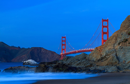 The Golden Gate Bridge in San Francisco as viewed from Marshall Beach as the night slowly makes its way in as the evening waves crash over the rocks on the beach (Clint Losee)