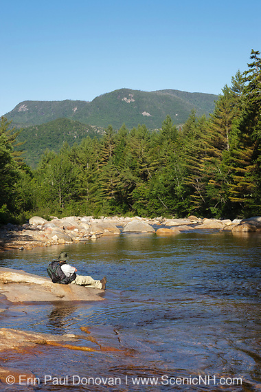 A hiker on the side of the East Branch of the Pemigewasset River in the Pemigewasset Wilderness in Lincoln, New Hampshire.
