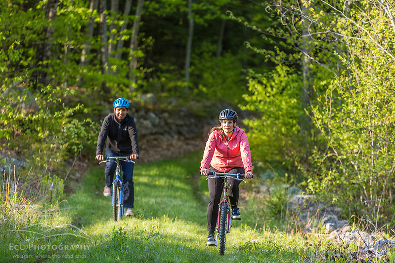 A couple mountain biking on a forest trail near Stonehouse Pond in Barrington, New Hampshire. (Jerry and Marcy Monkman)