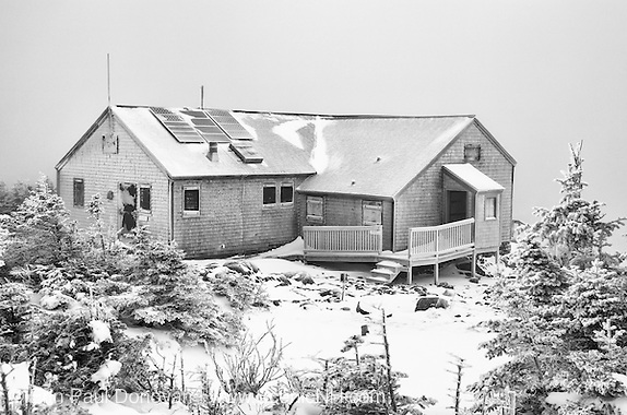 Black and white photo of Greenleaf Hut in extreme weather conditions during the winter months in the White Mountains, New Hampshire. On a clear day Mount Lafayette can be seen in the background.