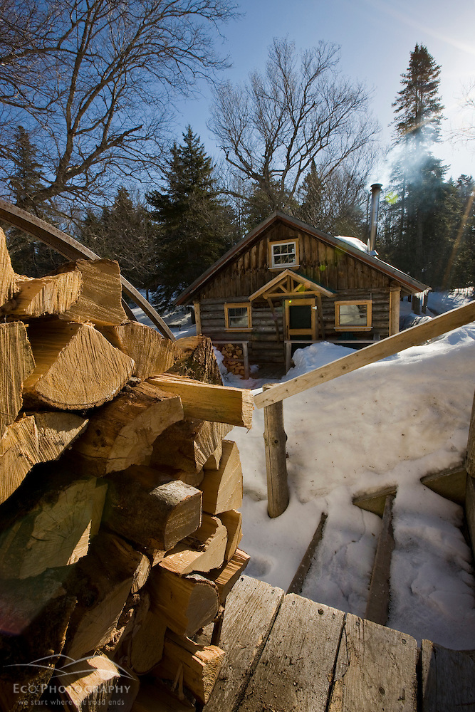 Split logs outside a cabin at Little Lyford Pond Camps near Greenville, Maine.  Winter. (Jerry and Marcy Monkman)