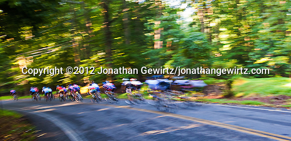 A group of recreational bicyclists passes the camera in a blur on its way down a hill in a wooded area. (© 2012 Jonathan Gewirtz / jonathan@gewirtz.net)