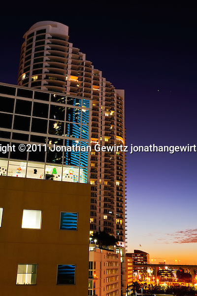 Twilight view of office and condo buildings near Miami's downtown, showing Christmas decorations and colorful reflections. (© Jonathan Gewirtz)