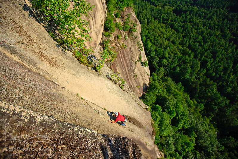 """A man climbs """"Top of the Prow"""" on Cathedral Ledge.  Echo Lake State Park in North Conway, New Hampshire.  White Mountains. (Jerry and Marcy Monkman)"""