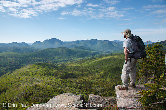 April history; a hiker takes in the view of the Pemigewasset Wilderness from the summit of Zeacliff during the summer months. This view point is along the Appalachian Trail in the White Mountains, New Hampshire. Much of this forest was logged during the East Branch & Lincoln Railroad era, which was a logging railroad in operation from 1893-1948.