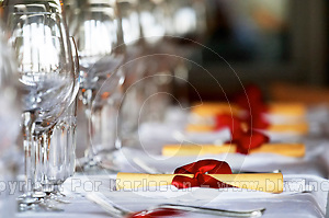 Table with knives, forks and wine glasses.