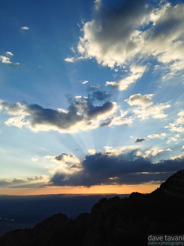 The sun dips behind a few clouds, as seen from Sandia Peak outside of Albuquerque, New Mexico. (Dave Tavani)