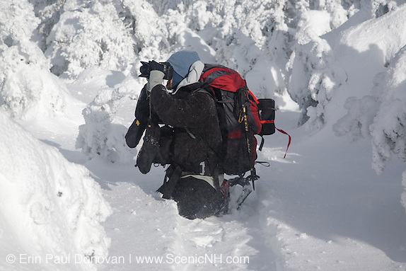 A hiker photographing along the Carter-Moriah Trail in winter conditions near the summit of Carter Dome in the White Mountains, New Hampshire.