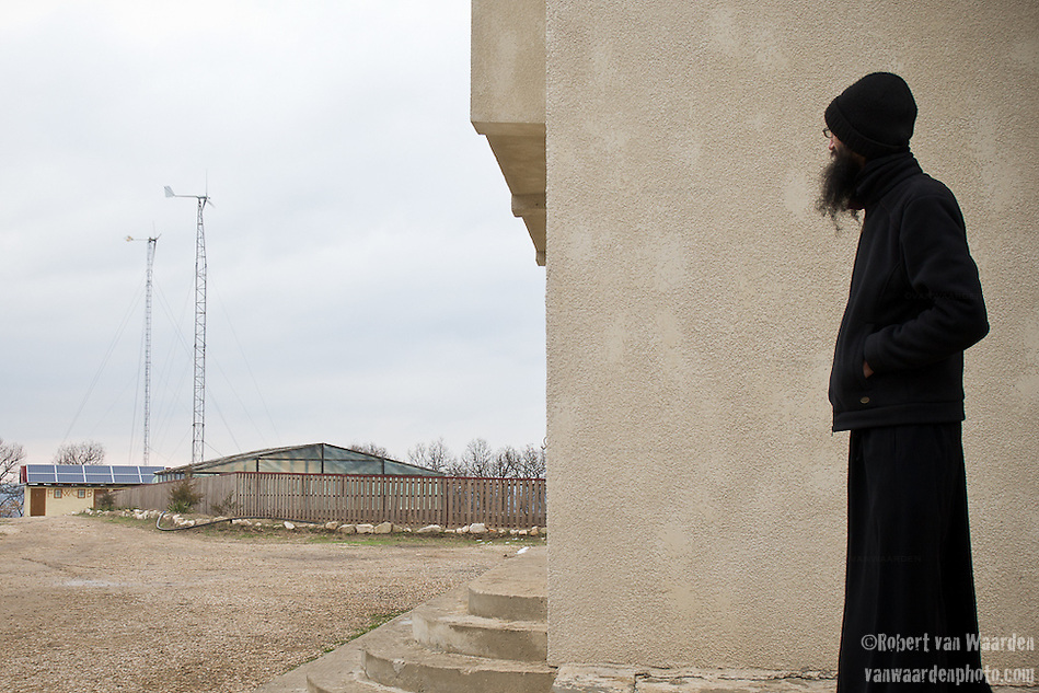 A monk at the Casian Monastery in Romania looks at the two wind turbines that are installed as part of the renewable energy system. (Robert van Waarden)