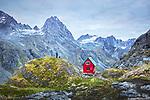 A hiker and his dog stand next to the Mint Hut overlooking the Talkeetna Mountains near Hatcher Pass, Alaska. (Seth K Hughes)