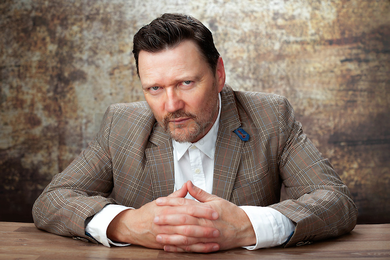 In this portrait of Ian Puleston-Davies the photographer with hands crossed on the table in front of him. (Colin Boulter)