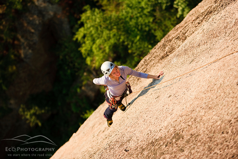 A woman rock climbing near the top of Cathedral Ledge.  Echo Lake State Park in North Conway, New Hampshire.  White Mountains. (Jerry and Marcy Monkman)