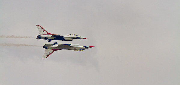 Two Thunderbird jets flying in formation, one of them inverted. (Clint Losee)