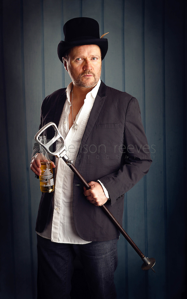 In the three quarter length portrait of Ian Puleston-Davies he is holding is late fathers walking can, wearing a top hat and holding a bottle of beer. These elements all work together to create a bedraggled look of a man on the edge (Colin Boulter)