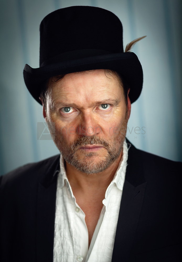 This portrait featuring Ian Puleston-Davies witch doctor style top hat with feather. An intense portrait with a sinister look of a man possessed. (Colin Boulter)