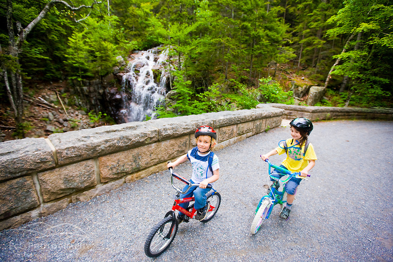 two young bike riders on a carriage road in Maine's Acadia National Park. Hadlock Brook, Waterfall Bridge. (Jerry and Marcy Monkman)