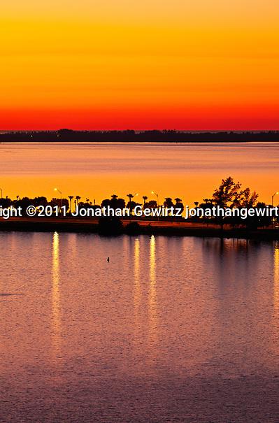 Red twilight immediate before sunrise, looking over Miami's Rickenbacker Causeway and Key Biscayne toward the Atlantic Ocean on New Year's Eve 2011. (© Jonathan Gewirtz)