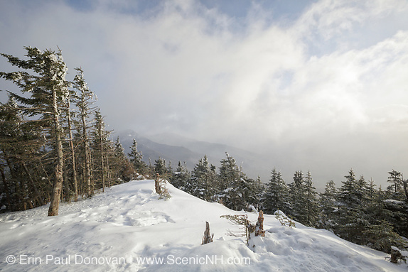 Windy conditions cause snow and clouds to blow across the mountains from the summit of Mount Tecumseh in Waterville Valley, New Hampshire USA during the winter months.