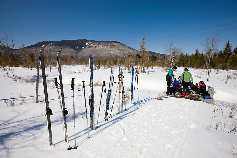 A group of cross-country skiers takes a lunch break on the Pleasant River Trail between West Branch Pond Camps and Little Lyford Pond Camps near Greenville, Maine.  Baker Mountain is in the distance. (Jerry and Marcy Monkman)