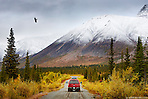 A red truck enters Wrangell-St. Elias National Park, Nabesna, Alaska with snow dusted mountains and autumn foliage covering the landscape. (Seth K Hughes)