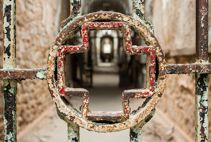 A cross adorns a metal gate to the medical ward inside Eastern State Penitentiary in Philadelphia, PA (Walter Arnold)